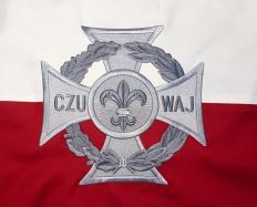 Krzyż harcerski na tle flagi